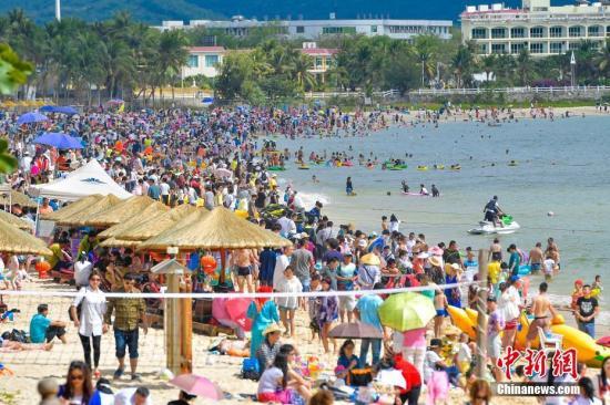 资料图:数万游客畅享三亚椰风海韵阳光沙滩。 中新社记者 骆云飞 摄