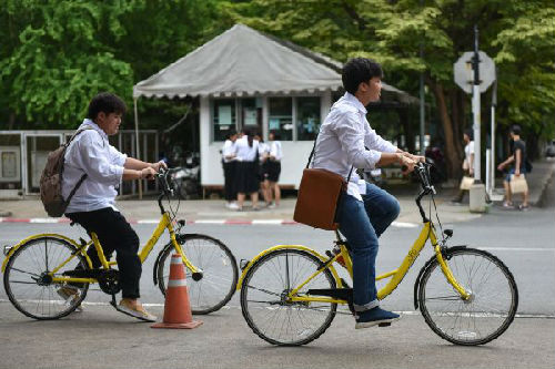 8月15日,在泰国曼谷的泰国国立法政大学,两名学生使用ofo小黄车出行。 新华社记者李芒茫摄