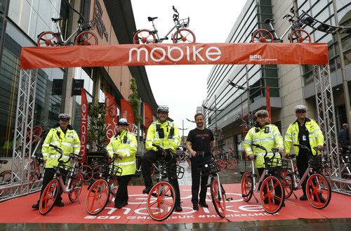 资料图片:2017年6月29日,在英国曼彻斯特,几名警员在摩拜单车投放仪式上合影。新华社发