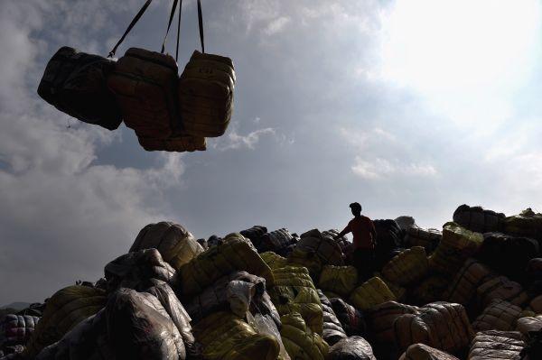 资料图片:2016年11月17日,事情职员在深圳土洋码头搬运走私废旧衣物。新华社记者 毛思倩 摄