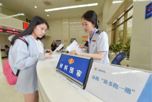 在福州地税综合办税中央办税服务厅,事情职员对纳税人质料举行预审,以节约其期待时间(7月18日摄)。新华社记者 宋为伟 摄