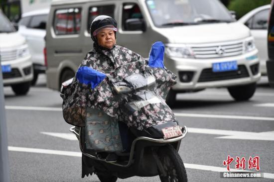 资料图:8月30日,成都市民增添衣物出行。 中新社记者 张浪 摄