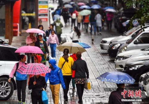 9月24日,新疆乌鲁木齐市降下秋雨,外出民众打着雨伞快步前行。 中新社记者 刘新 摄