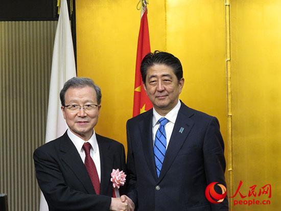 中国驻日本大使程永华与安倍首相在会场进口处合影。 滕雪摄