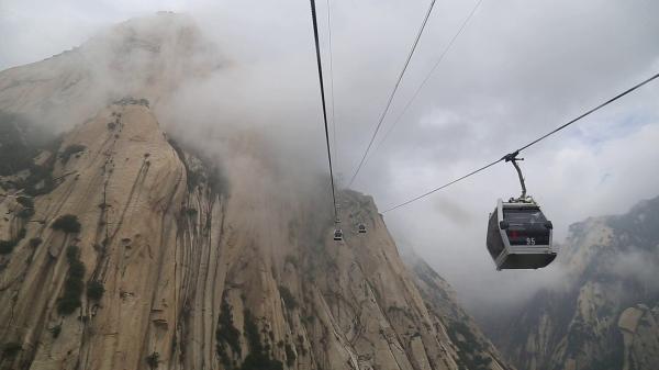 前去西峰的缆车穿越在雨雾中。