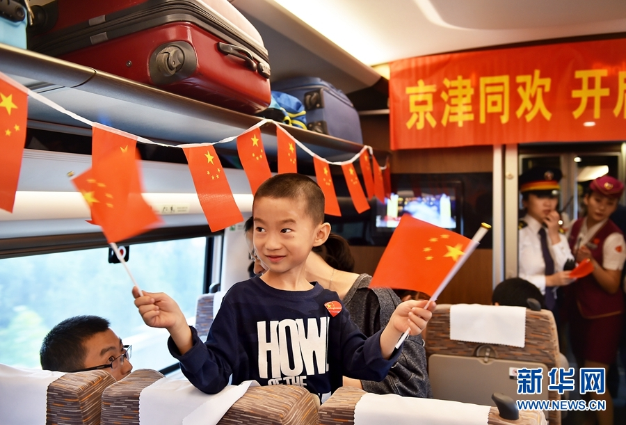 """10月1日,乘坐京津城际中国标准动车组""""复兴号""""列车的小旅客与乘务人员共同为祖国成立68周年华诞庆生。"""