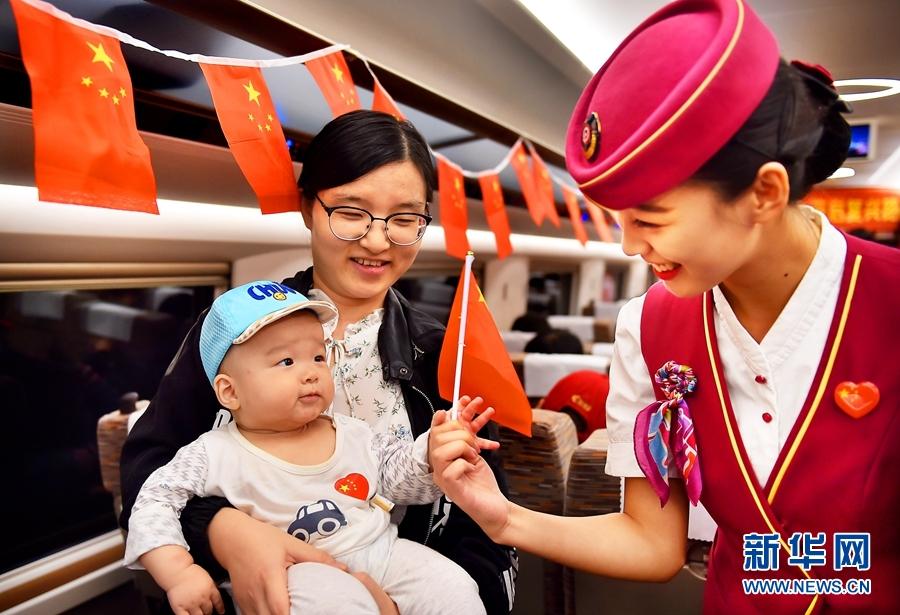 10月1日,北京铁路局天津客运段京津城际包乘组乘务员与旅客互动向旅客赠送小国旗为祖国庆生。