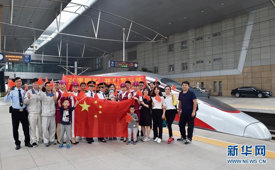 """10月1日,值乘C2025次京津城际中国标准动车组""""复兴号""""的乘务人员与旅客在天津站站台上合影留念,庆祝祖国成立68周年华诞。"""