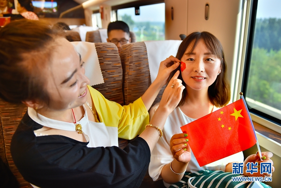 """10月1日,乘坐京津城际中国标准动车组""""复兴号""""列车的旅客共同为祖国成立68周年华诞庆生。"""