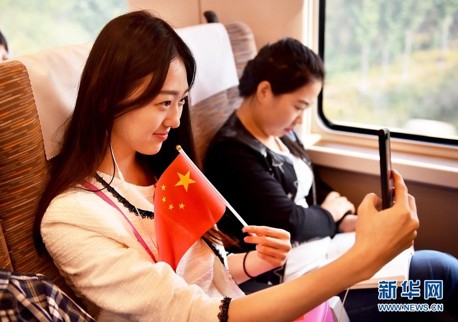 """10月1日,乘坐京津城际中国标准动车组""""复兴号""""列车的旅客与乘务人员共同为祖国成立68周年华诞庆生,用手机自拍留影。"""