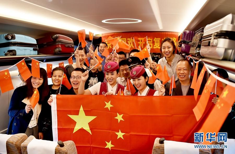 """10月1日,乘坐京津城际中国标准动车组""""复兴号""""列车的旅客与乘务人员挥舞国旗互动共同为祖国成立68周年华诞庆生,并合影留念。"""