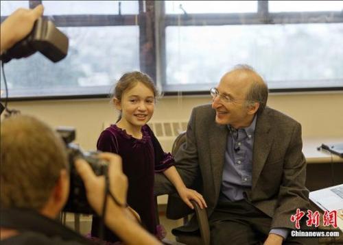 2011年10月4日,加州大学伯克利分校天体物理学家波尔马特和他8岁的女儿诺阿在办公室里。中新社发 陈钢 摄