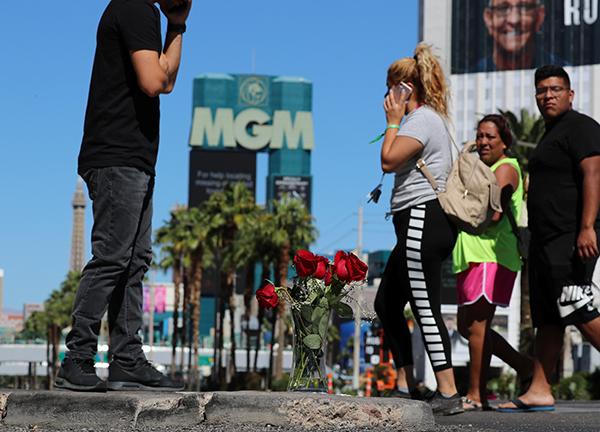10月2日,美国拉斯维加斯,人们从枪击事件现场附近放置的一束鲜花旁走过。 新华社 图
