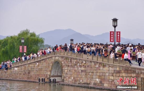 10月3日,国庆长假第三天,大量游客涌入西湖断桥。 中新社记者 李晨韵 摄