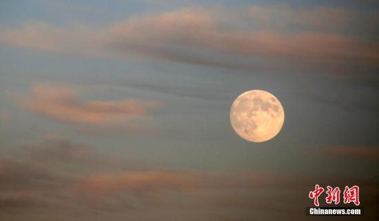 资料图:一轮圆月高挂天边,在晚霞的映衬下下十分俏丽。 中新社发 卜向东 摄 图片来源:CNSPHOTO
