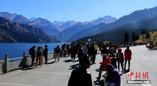 10月4日,新疆天山天池湖畔阳光明媚、秋色尽染,来自国内外游人徜徉在如画的湖光山色里,预计全天旅游接待量近万人。甄梅 摄