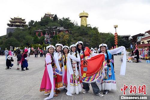 10月3日,着藏族服饰的游客在独克宗古城月光广场上合影。 中新社记者 李进红 摄