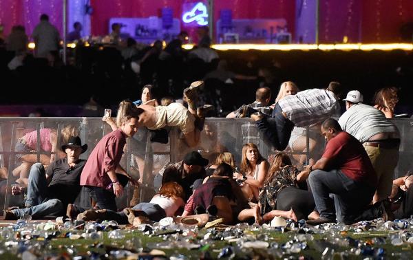 10月1日,拉斯维加斯枪击案现场,人们翻越围栏寻找掩蔽。 视觉中国 图