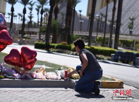 10月3日,位于拉斯维加斯市中心的事发区域依然严密封锁。在现场警戒线内侧,摆放着民众送来的鲜花和气球、蜡烛等。图为一位拉斯维加斯居民前来向遇难者献花致哀。 中新社记者 张朔 摄