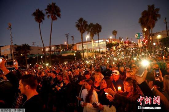 当地时间2017年10月4日,美国加州曼哈顿海滩,民众和遇难者的亲人朋友集会,手持烛光和灯光,悼念日前拉斯维加斯枪击案遇难者。