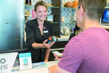 美国纽约SPG联盟四季酒店前台服务员使用POS机接受中国游客支付宝扫码付款。