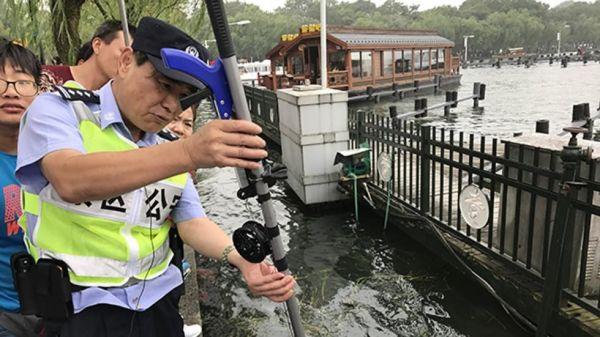 周翔军警官用他自制的工具帮助游客打捞掉进西湖里的手机(香港《南华早报》网站)