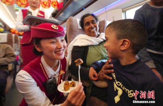 """10月4日,正值中国传统节日中秋节,在北京南开往上海虹桥的G13次""""复兴号""""高铁列车上,乘务组给旅客发月饼、猜灯谜,共度中秋。图为列车长于晓雪为一位外籍小乘客发月饼。 中新社记者 贾天勇 摄"""