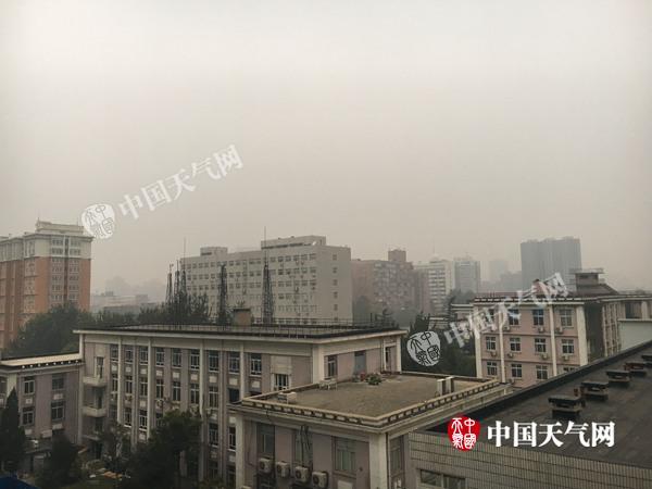 今晨7时左右北京天空阴沉,远处楼房已模糊。