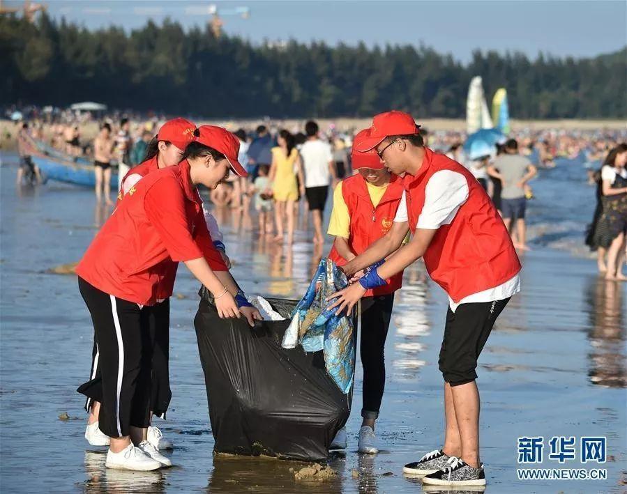 ▲國慶期間環保志願者在沙灘收集垃圾。圖據新華網