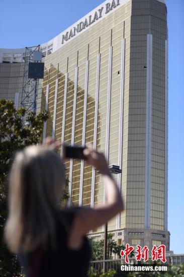当地时间10月4日上午,美国拉斯维加斯曼德勒海湾酒店金碧辉煌的外墙上,两个黑洞洞的破损窗口触目惊心。 中新社记者 张朔 摄