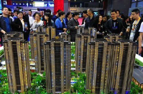 资料图:参观者在江苏无锡举办的房展会上观看一家房地产商的楼盘模型。