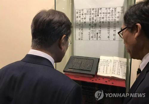 资料图片:文在寅(左)在出席联大期间参观陈列于联合国总部的《月印千江之曲》。(图片来源:韩联社)