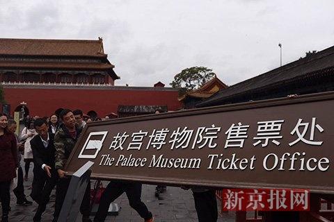 工作人员摘下故宫博物院售票处的牌匾。