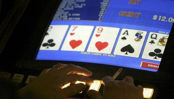资料图片:一名赌客在玩电子扑克(video poker)赌博机。来源:东方IC