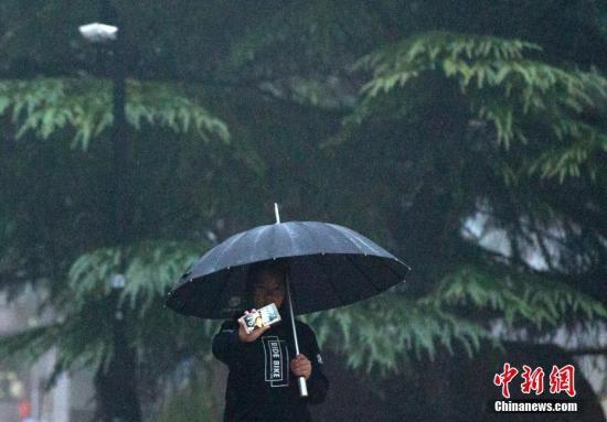 资料图:市民在雨中自拍。 中新社记者 刘关关 摄