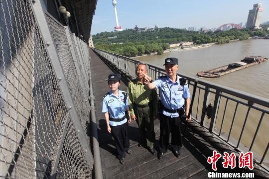 """图为,黄小勇带着""""徒弟""""宋晨曦和退休老民警查看大桥设施 胡金力 摄"""