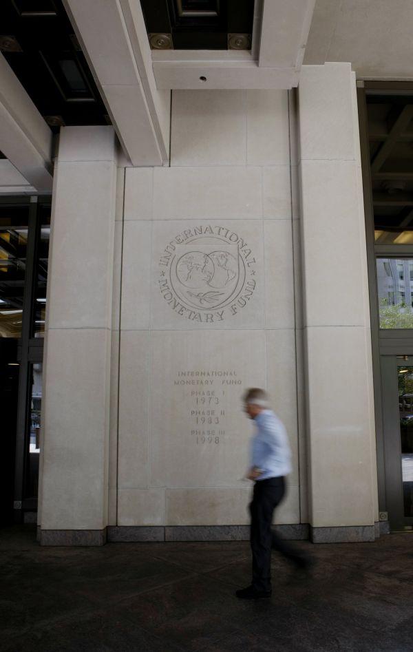 资料图片:在美国首都华盛顿,一名男子经过位于市区的国际货币基金组织大楼。新华社记者 方喆 摄