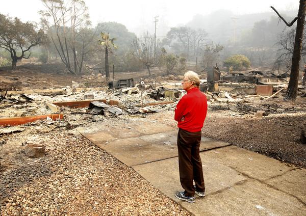 查尔斯的大儿子麦克(Mike Rippey)望着被大火摧毁的老家 。