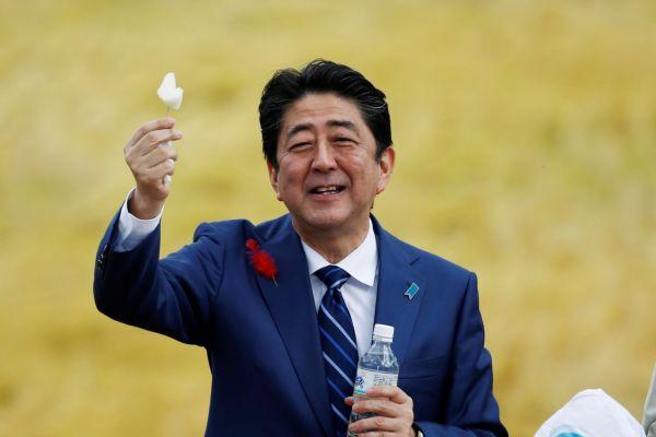 10月10日,日本首相安倍晋三在福岛的竞选集会上举着当地支持者送的一块梨。(路透社)