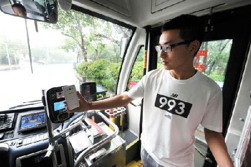 资料图片:7月2日,乘客在青岛交运31路公交车上使用手机支付公交车费。新华社发