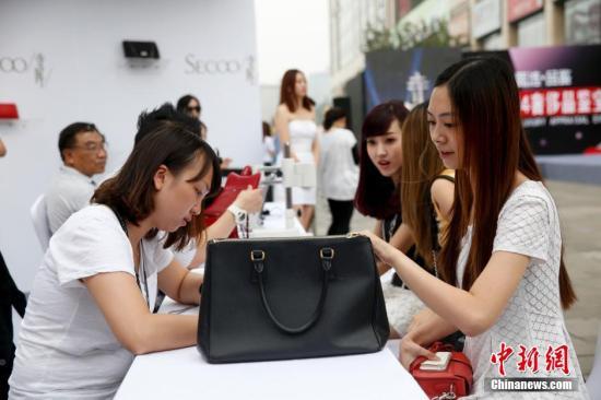 资料图:在北京崇文门街边举行的寺库奢侈品鉴宝会,吸引众多路人排队鉴宝。 中新社发 杜洋 摄