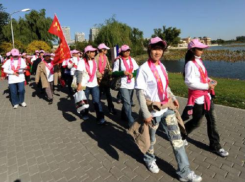 """资料图片:2008年10月26日,由中国红十字基金会主理的""""粉红丝带 心系你我——2008爱的行走""""大型公益健走运动在北京向阳公园举行,近5000名社会各界爱心人士用现实行动呼吁民众关注女性康健,资助乳腺癌患者。新华社记者 金良快摄"""