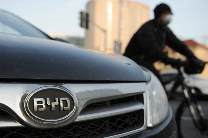 ▲资料图片:中国上海,一个戴着口罩的人骑车经过一辆比亚迪汽车。(法新社)