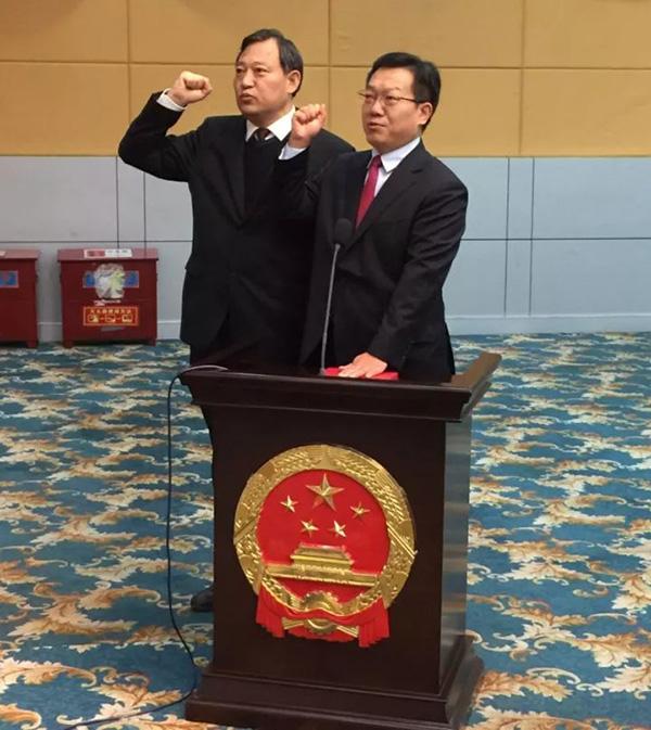 """景劲松(右)、谢松民(左)面对国徽向宪法庄严宣誓。本文图片均来自南阳日报社微信公众号""""南阳报业传媒"""""""