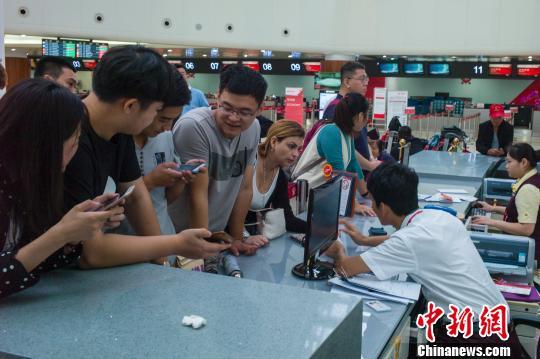 图为海口美兰国际机场航站楼内服务台群集了前来改签问询的游客。 骆云飞 摄