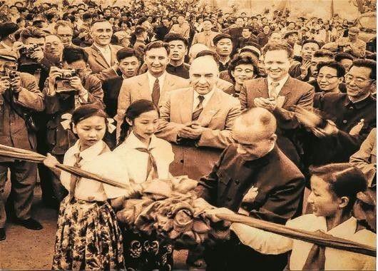 图为:1957年10月15日,时任国务院副总理李富春为武汉长江大桥通车剪彩时,李素荣(右下角)在一旁牵彩。