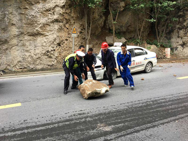 交警与路过驾驶员一道将石头搬开。