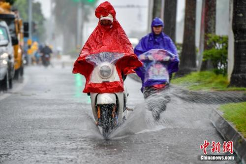 10月15日,海口民众雨中涉水骑行。中新社记者 骆云飞 摄