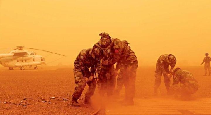 ▲资料图片:中国赴马里维和队伍工兵分队在沙尘暴中紧迫睁开机场直升机停机坪建设使命。