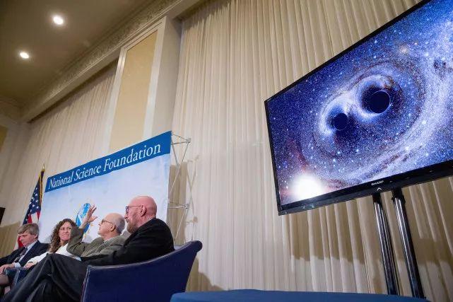 显示屏展现出两个黑洞合并产生的引力波信号图像。